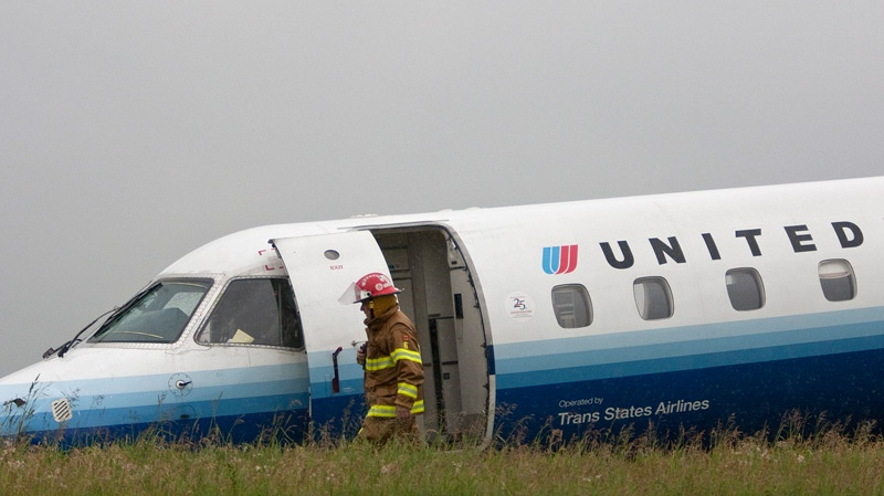 An Ottawa firefighter walks past a United Airlines Express airplane which slid off of the runway at Ottawa International Airport in Ottawa on Wednesday, June 16, 2010. (Pawel Dwulit / THE CANADIAN PRESS)