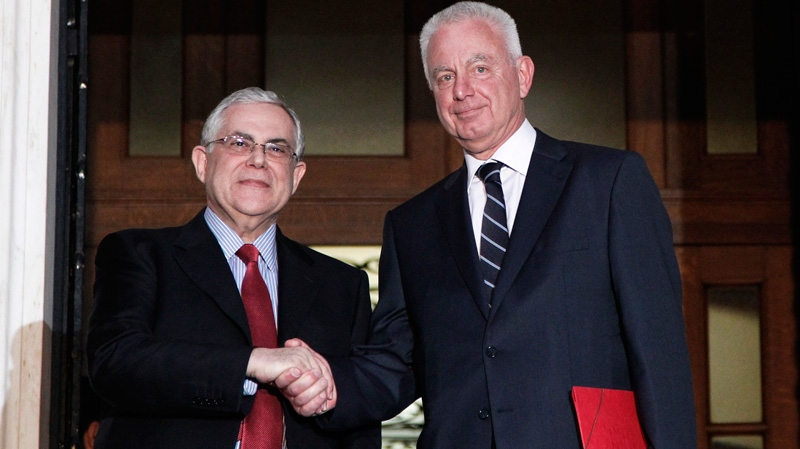 Newly appointed caretaker Prime Minister Panagiotis Pikrammenos, right, shakes hands with outgoing Prime Minister Lucas Papademos prior their meeting and after his swearing-in ceremony at the Presidential Palace, in Athens on Wednesday, May 16, 2012. (AP / Petros Giannakouris)