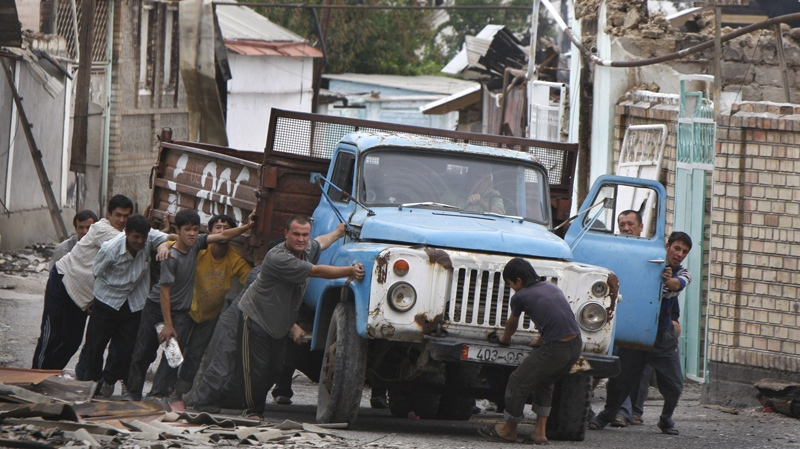 Uzbek men push a truck as they build a barricade in the Uzbek district in the southern Kyrgyz city of Osh, Thursday, June 17, 2010. (AP / Sergei Grits)