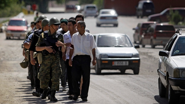 Kyrgyz and ethnic Uzbek men walk along a street of Suzak, the Uzbek neighbourhood near the southern Kyrgyz city of Jalal-Abad, Kyrgyzstan, Friday, June 18, 2010, as they perform joint Kyrgyz-Uzbek patrol. (AP / Sergey Ponomarev)