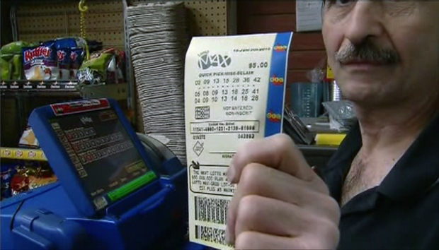 A Convenience Store Owner Holds Up A Lotto Max Ticket In Toronto Friday June
