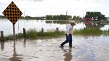 Don Byspalko walks through receding flood waters in front of his house after flooding in Irvine, Alta., Saturday, June 19, 2010. Some residents of the small hamlet had to be rescued from flooded homes on Friday. The Trans Canada highway from the Saskatchewan border to Dunmore, Alta., remains closed. THE CANADIAN PRESS/Jeff McIntosh