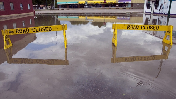 Signs block a flooded road in the South Flats area of Medicine Hat, Alta., Saturday, June 19, 2010. (Jeff McIntosh / THE CANADIAN PRESS)