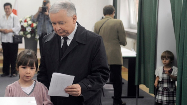 Presidential candidate Jaroslaw Kaczynski, twin brother of the late President Lech Kaczynski killed in a plane crash, prepares to cast his ballot, accompanied by his brother's grand daughters Eva, left, and Martyna, right, in the presidential election in Warsaw, Poland, Sunday, June 20, 2010. (AP / Alik Keplicz)