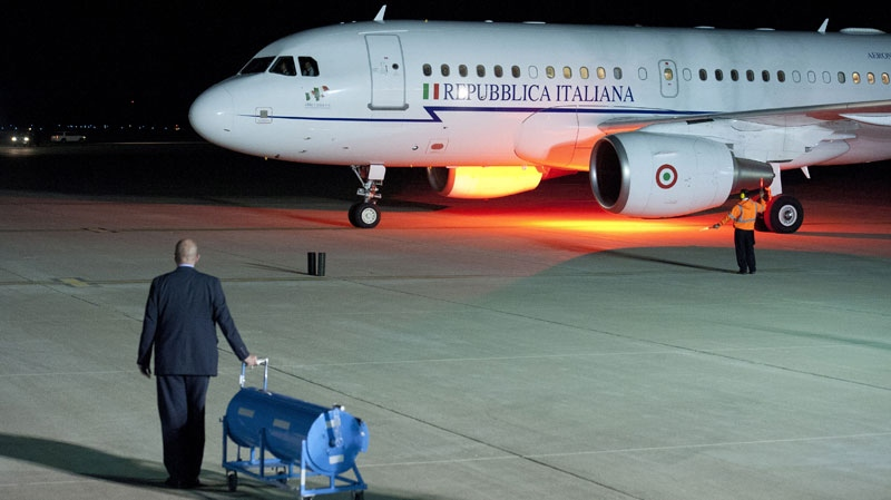 A State Department official waits with a red carpet roller as the airplane caring Italian Prime Minister Mario Monti arrives at Dulles International Airport in Sterling, Va., Friday, May 18, 2012 for the G8 Summit at Camp David.