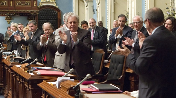 Quebec Premier Jean Charest, left applauds his Education Minister Michele Courchesne (hidden) the special legislation vote on Friday May 18, 2012 in Quebec City. THE CANADIAN PRESS/Clement Allard
