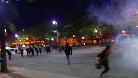 A masked protester runs from a line of Montreal riot police in this photo taken from video on Friday, May 18, 2012.