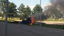 Smoke billows from the small plane after it crashed in a parking lot near Buttonville Airport in Markham, Ont. (Shiraz Sarangi / MyNews.CTV.ca)