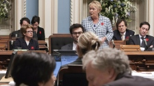 Quebec Premier Jean Charest discusses with his Education Minister Michele Courchesne (foreground) before the vote on the emeergency law, as Opposition Leader Pauline Marois makes closing speech on Friday May 18, 2012 in Quebec City .THE CANADIAN PRESS/Clement Allard