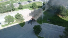 The smoking remains of a plane are seen near the Buttonville Airport on Sunday, June 20, 2010. The photo was taken by witness Amit Kohli, who was working on the eighth floor of a nearby office building at the time of the crash.
