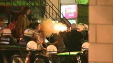 In this image taken from video, police are seen pepper spraying patrons at a bar in Montreal, Que. Saturday, May 19, 2012.