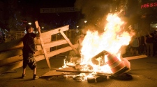 Protesters add to a fire during a demonstration in Montreal, Saturday, May 19, 2012.