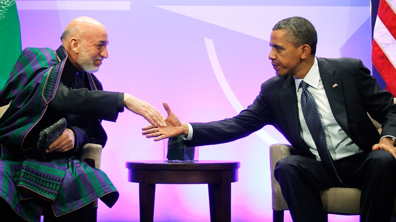 President Barack Obama, right, shakes hands with with Afghan President Hamid Karzai, left, during their meeting at the NATO Summit