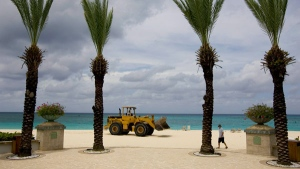 A bulldozer passes on the beach in front of a seaside resort on Seven Mile Beach, Grand Cayman Island, Friday, Aug. 29, 2008. (AP / Brennan Linsley)