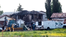 Workers clean up after a house exploded killing two and injuring several more in a northeast Edmonton neighbourhood on Sunday June 20, 2010. (Ian Jackson / THE CANADIAN PRESS)
