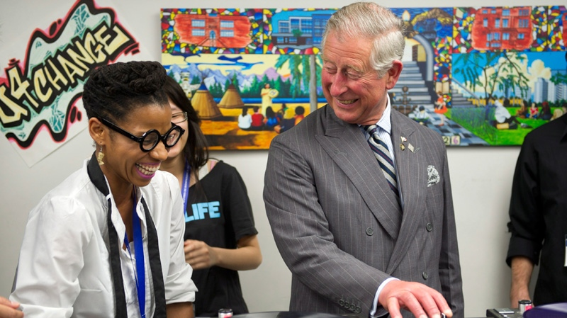 Prince Charles learns how to scratch and fade with a turntable as he tours an employment skills workshop in Toronto, on Tuesday, May 22, 2012. (Paul Chiasson / THE CANADIAN PRESS)