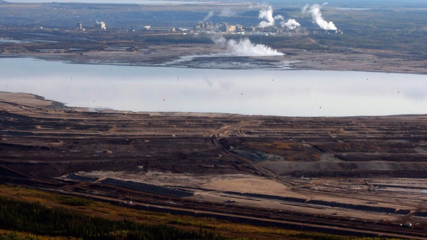 This aerial photo shows a tar sands tailings pond at a mine facility near Fort McMurray, Alta, Sept. 19, 2011. (Jeff McIntosh / THE CANADIAN PRESS)
