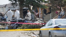 Edmonton Police Service investigators comb through through the rubble of a residential explosion scene, in an Edmonton neighbourhood, Monday June 21, 2010. (John Ulan / THE CANADIAN PRESS)