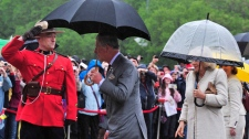 Prince Charles and his wife Camilla, the Duchess of Cornwall, arrive in the rain at the legislature in Regina on Wednesday, May 23, 2012.  (Paul Chiasson / THE CANADIAN PRESS)