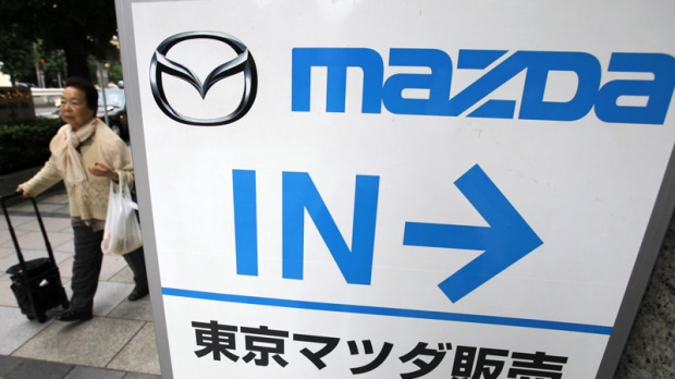 A woman walks near a Mazda Motor Corp.'s showroom in Tokyo, Wednesday, May 23, 2012. Mazda and Fiat SpA are working together on developing and manufacturing a roadster, or two-seater convertible, although the automakers will come up with different, distinctly styled models. Both sides said in a release Wednesday they had signed an agreement to work together, but each manufacturer will use its own engine and styling.