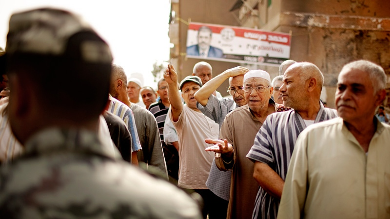 Egyptian voters argue with a solider as they wait cast ballots in Basateen a southern suburb of Cario, Egypt on Wednesday, May 23, 2012. (AP / Pete Muller)