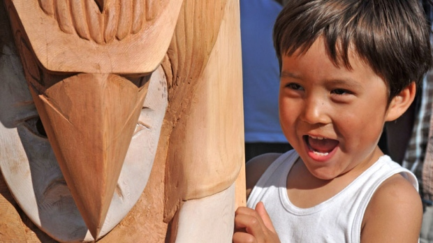 A young boy checks out Hjalmer Wenstob's nearly completed totem during an unveiling on Meares Island, B.C., May 12, 2012. The completed totem will be on display at Vancouver International Airport beginning Friday for the next year.