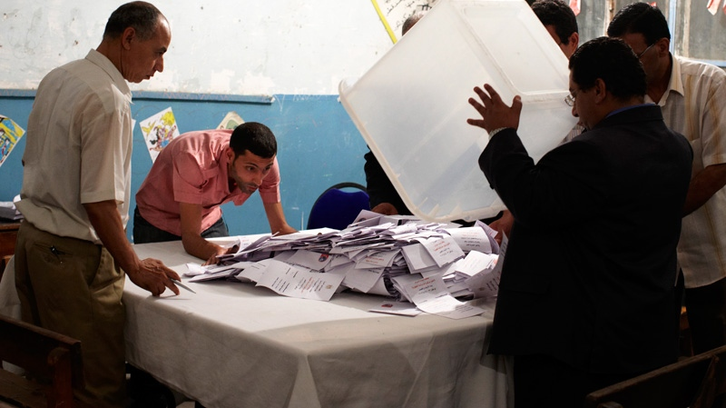 An Egyptian election official, right, opens a ballot box before counting the votes following the end of the two day presidential election in Cairo, Egypt