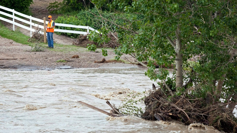 A county employee inspects a property that is in danger of collapsing into Ross Creek during flooding east of Medicine Hat, Alta., Saturday, June 19, 2010. (Jeff McIntosh / THE CANADIAN PRESS)