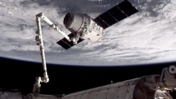 The SpaceX Dragon commercial cargo craft is shown after it was grappled by the Canadarm2 robotic arm and connected to the International Space Station, Friday, May 25, 2012. (AP / NASA)