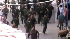 This image made from amateur video shows police running toward a protest in Damascus, Syria, released by Shaam News Network and accessed Friday, May 25, 2012. (AP / Shaam News Network)