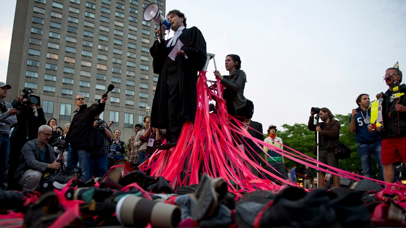 A lawyer addresses students banging on pots and pans following a march of hundreds of lawyers in the streets of Montreal to protest against Quebec's Bill 78 aimed at controlling student demonstrations Monday, May 28, 2012 in Montreal. THE CANADIAN PRESS/Paul Chiasson