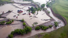 A farm sits flooded along the Trans Canada highway near Irvine, Alta., parts of the highway remain closed and some are underwater east of Medicine Hat, Alta., Monday, June 21, 2010. (Jeff McIntosh / THE CANADIAN PRESS)