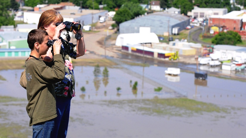 Blanche Leist and her son David survey the flood damage in the South Flats looking from Scholten Hill in Medicine Hat, Aberta on Sunday June 20, 2010. (Medicine Hat News, Emma Bennett / THE CANADIAN PRESS)
