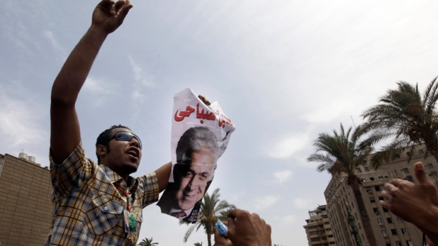 An Egyptian man holds a poster of former presidential candidate Hamdeen Sabahi, during a protest against the results of presidential elections at Tahrir Square, the focal point of Egyptian uprising, in Cairo, Egypt