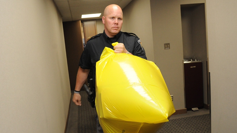 A police officer removes a package containing a human foot from the Conservative Party headquarters in Ottawa on Tuesday, May 29, 2012. (Sean Kilpatrick / THE CANADIAN PRESS)