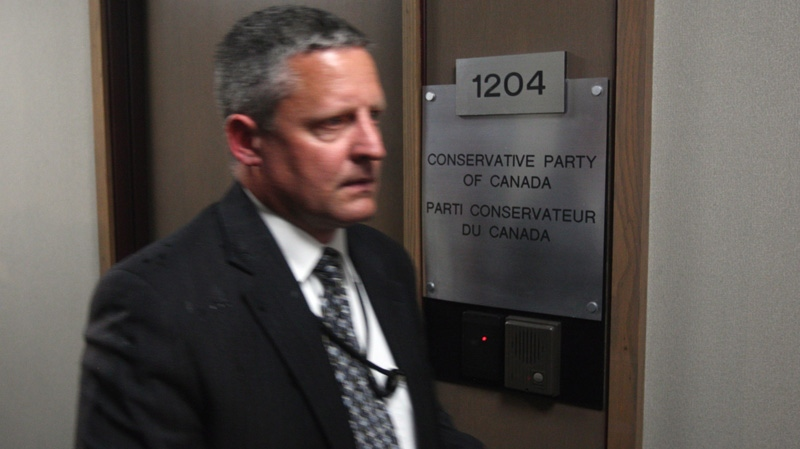A security personnel member walks past a door at the Conservative Party of Canada office in Ottawa, Tuesday, May 29, 2012. (Adrian Wyld / THE CANADIAN PRESS)