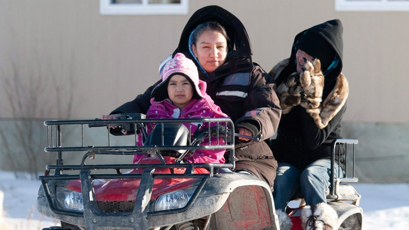 A woman takes children to school on a four wheel vehicle following their lunch break in Attawapiskat, Ont., Tuesday, Nov. 29, 2011. (Adrian Wyld / THE CANADIAN PRESS)