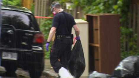 A police officer removes a garbage bag containing a human torso that was found in a suitcase in Montreal, Tuesday, May 29, 2012. (CTV News)