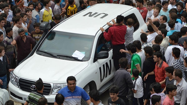In this citizen journalism image, Syrians gather around a U.N. observers vehicle during a demonstration in Kfarnebel, Idlib province, northern Syria on Tuesday, May 29, 2012. (AP / Edlib News Network)