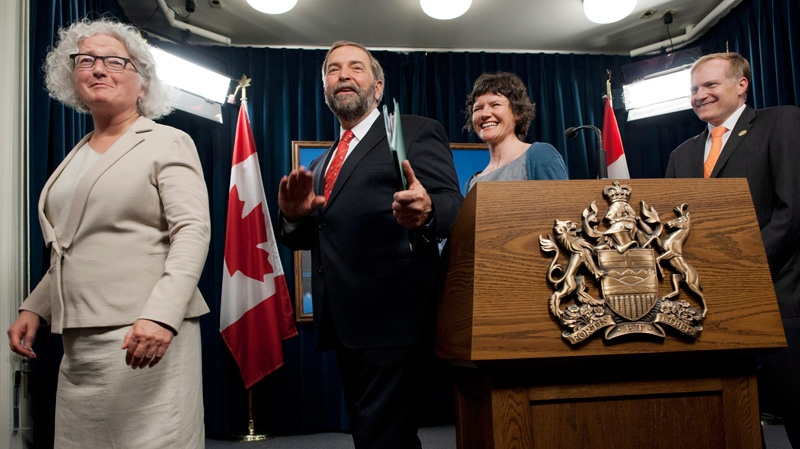 Federal NDP Leader Tom Mulcair, centre, surrounded by Alberta NDP MP Linda Duncan, left, environment critic Megan Leslie, centre right, and energy critic Peter Julian, jokes with reporters as he departs a media availability about his tour of oilsands operations north of Fort McMurray, at the Alberta Legislature, in Edmonton, on Thursday, May 31, 2012. (John Ulan / THE CANADIAN PRESS)