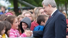 Prime Minister Stephen Harper shakes hands with a young girl before taking part in Canadian Forces Day celebrations in North Bay, Ont., on Friday, June 1, 2012. (Adrian Wyld / THE CANADIAN PRESS)