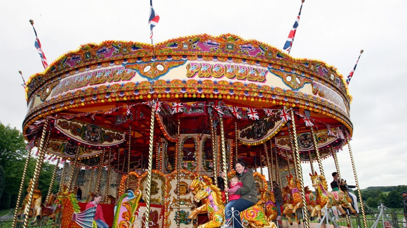 Sarah Willcock and her daughter Nieva, are seen enjoying a ride on a carousel at a old style traditional fairground in honor of Britain's Queen Elizabeth II Diamond Jubilee inthe grounds of Alnwick Castle, Saturday, June 2, 2012. AP Photo/Scott Heppell)