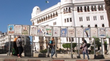 Algerians walk by posters for election lists displayed in front of the main post office in downtown Algiers Monday April 30, 2012. (AP Photo / Paul Schemm)