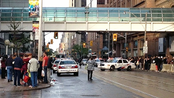 People gather outside of the Eaton Centre after a shooting at the mall's food court on Saturday, June 2, 2012.
