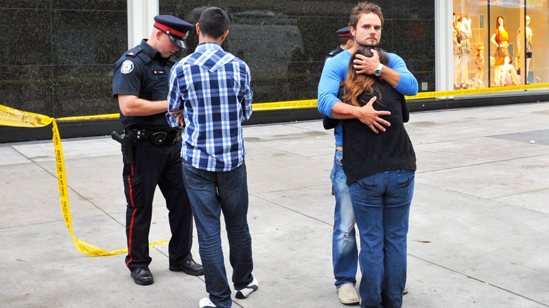 A couple hug as a police officer questions a man outside the Eaton Centre shopping mall in Toronto, Saturday, June 2, 2012. (Victor Biro / THE CANADIAN PRESS)