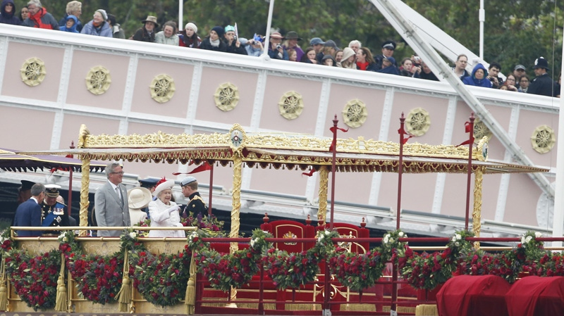 Queen Elizabeth II, centre, points down river while standing on the royal barge, the principal boat of a flotilla of 1,000 vessels, on the River Thames, during a river pageant to celebrate the Queen's Diamond Jubilee in London