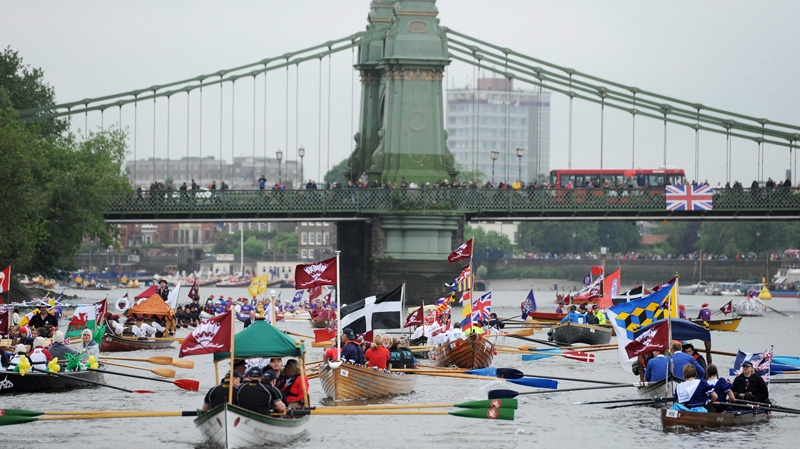Rowing boats begin to gather near Hammersmith Bridge on the River Thames, during the Diamond Jubilee river pageant in London