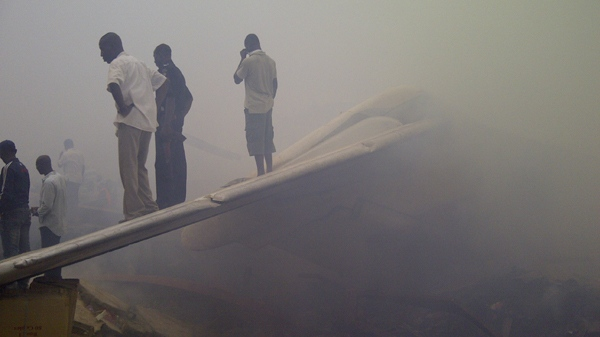 Onlookers stand on the tail wing of a crashed passenger plane in a neighborhood just north of Murtala Muhammed International Airport, in Lagos, Nigeria, Sunday, June 3, 2012. (AP / Jon Gambrell)
