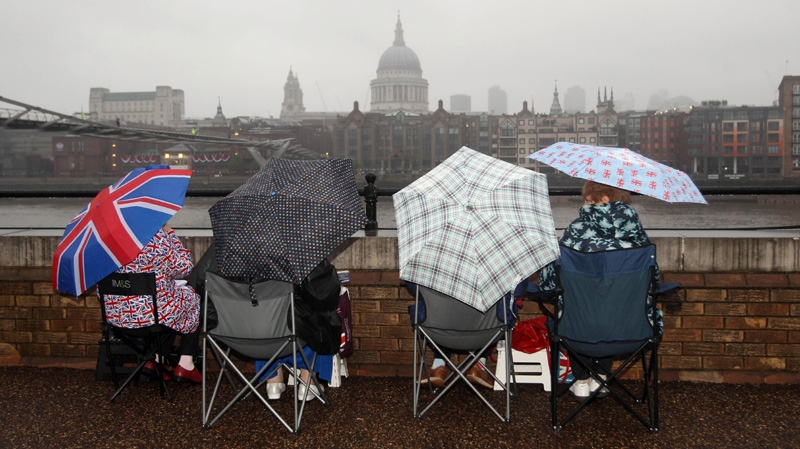 Royal revellers wait in the rain on the South Bank of the river Thames, London, several hours before the start of the Diamond Jubilee river pageant Sunday June 3, 2012.