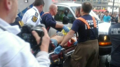 A victim is seen being rushed to the hospital following a shooting at Eaton Centre in Toronto, Saturday, June 2, 2012.